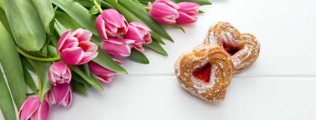 Bouquet of pink tulips with two heart shaped cake . Valentines day background.