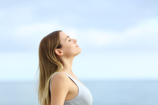 Profile of relaxed girl breathing fresh air on the beach