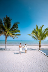 couple on the beach with palm tree and bleu ocean in Thailand Chumphon area during sunset at Arunothai beach