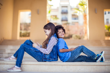 Two kids boy and girl playing with tablet outdoor. Children and gadget addiction concept