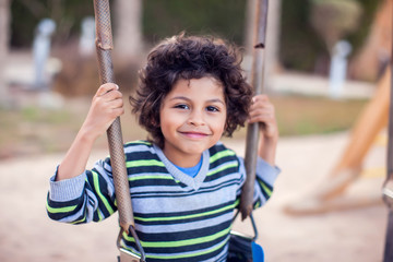 A smiling kid boy on a swing. Childhood and activity concept