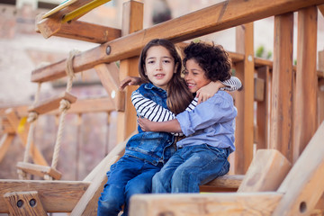 Two smiling kids friends boy and girl sitting on playground outdoor. Childhood and friendship...
