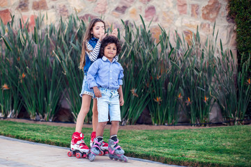 Two happy kids boy and girl roller skate in the park. Children and activity concept