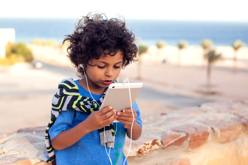 Kid boy playing with tablet outdoor. Children and gadget addiction concept