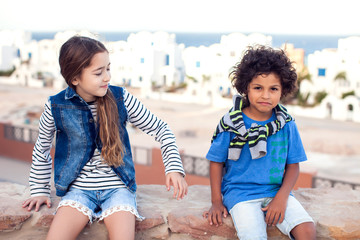 A portrait of smiling kid boy and girl outdoor. Children and emotions concept