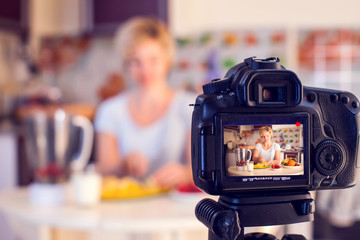 Woman food blogger cooking in front of camera and recording video. People, hobby and media concept