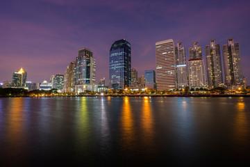 Scenic view of modern skyscrapers behind a lake at the Benjakiti (Benjakitti) Park in downtown Bangkok, Thailand, at dusk.