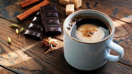 Coffee and spices star anise, cinnamon sticks, cardamom pods and dark chocolate bark on wooden table. Breakfast concept