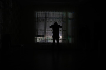Silhouette of a man standing at a window inside the room. Fantasy picture with old vintage lantern at the window inside dark room.