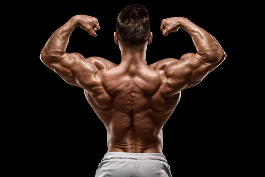 Muscular man showing back muscles rear view, isolated on black background. Strong male naked torso