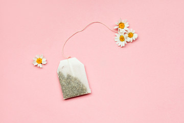 tea time, chamomile tea bag and fresh flowers on pastel pink background, flat layout