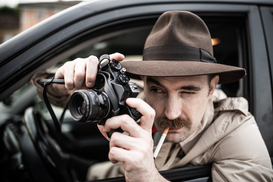 Paparazzo photographer, detective using camera in his car
