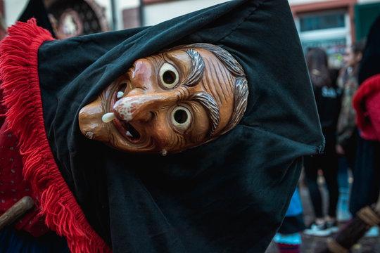 Troepfle Hexen aus Bad Rippoldsau - Hübsche Hexe mit schwarzer Kopfhaube und rot, blauem Gewand schaut frech mit geneigtem Kopf in die Kamera. Bei Fastnachtumzug in Staufen Süd Deutschland.