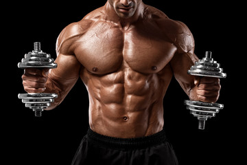 Muscular man showing muscles and abs isolated on black background. Strong male naked torso working...