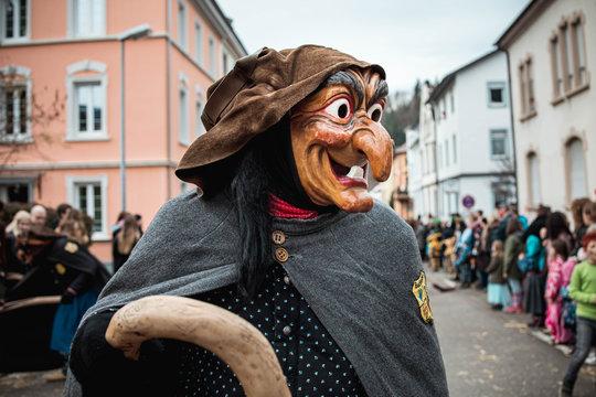 Schlosshexe aus Buchholz - Lustige Hexe mit großen Augen und langer Nase in dunklem Gewand und mit krumen Besen. Bei Fastnachtumzug in Waldkirch Süd Deutschland.
