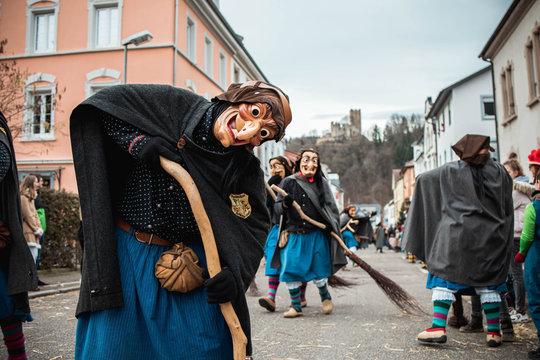 Schlosshexe aus Buchholz - Lustige Hexe mit großen Augen und langer Nase posiert vor schöner Stadtkulisse und einer Burg im Hintergund. Bei Fastnachtumzug in Waldkirch Süd Deutschland.