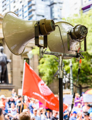 Horn speakers on a tall stand are being used to address the public at a political street rally