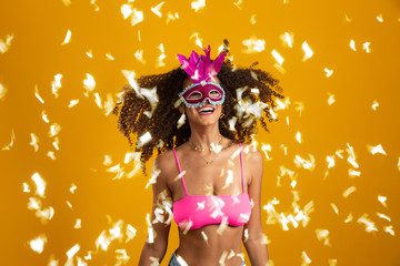 Beautiful woman dressed for carnival night. Smiling woman ready to enjoy the carnival with a colorful mask and confetti.