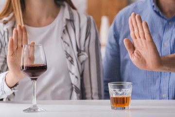 Couple refusing to drink wine and whiskey. Concept of alcoholism