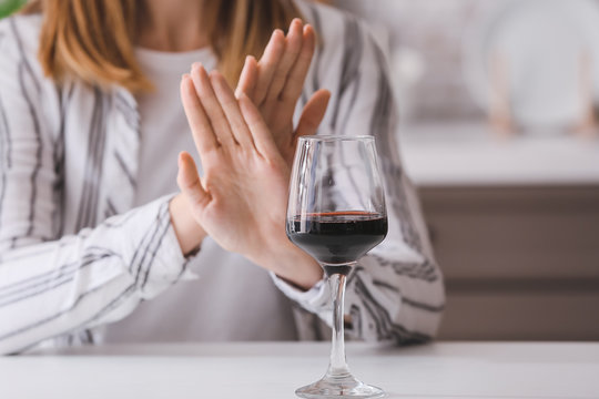 Woman refusing to drink wine at home. Concept of alcoholism