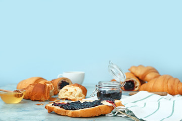 Tasty sweet croissants with jam on color background
