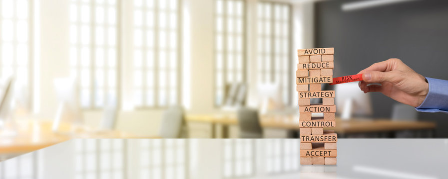 risk management concept. pull the risk management block through the wooden block tower