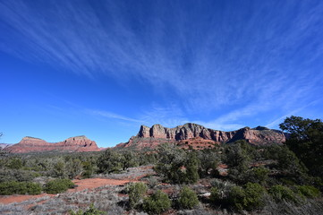 Red rock formations near Sedona, Arizona under wispy high altitude clouds on a clear winter morning.