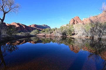 Red rock formations reflected in tranquil pond in Sedona, Arizona backcountry on clear cloudless winter afternoon.