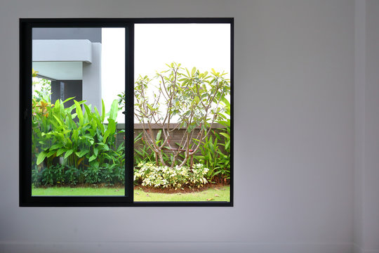slide glass window on white wall interior in modern empty room with small garden landscaping outside a new house