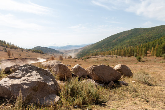 The beautiful landscape of Mongolia. Stones in the foreground and the dust from the unsealed rod beside . Dry grass in the barren landscape of Mongolians steppe.