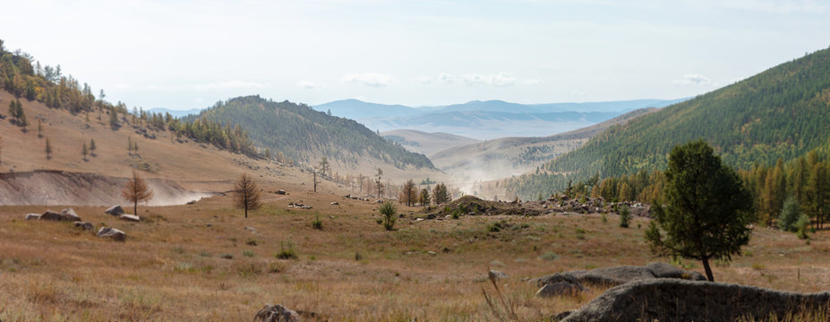 Panoramic view over the landscape of central Mongolia. The unsealed road to Ulaan Batar meanders through the landscape like a dusty rope or tape. The sand dust is visible on the horizon.