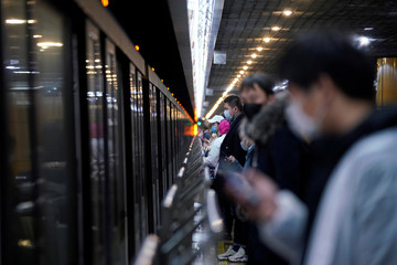 People wearing face masks are seen at a subway station in the morning after the extended Lunar New Year holiday caused by the novel coronavirus outbreak, in Shanghai