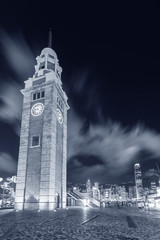 Fototapete - Old clock tower and skyline in Hong Kong city at night