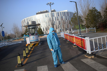 Security guard wearing a protective suit holds a thermometer in front of the entrance to the China Transinfo Technology Co, in the morning after the extended Lunar New Year holiday caused by the novel coronavirus outbreak, in Beijing