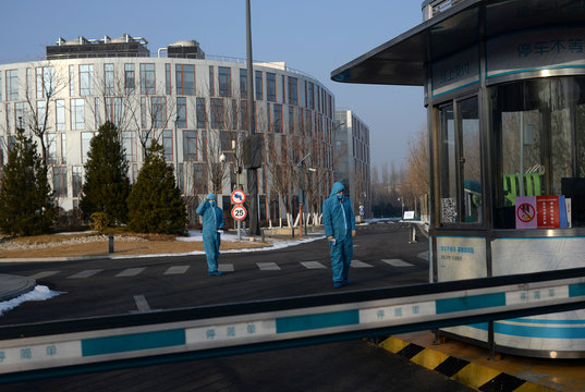 Security guards wearing a protective suit and a face mask stand as they hold thermometers at the entrance to the China Transinfo Technology Co, in the morning after the extended Lunar New Year holiday caused by the novel coronavirus outbreak, in Zhongguanc