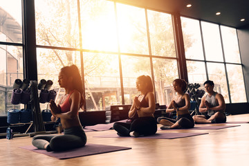 Group of Asian women and man doing pilates lying on yoga mats in aerobics class. Young sporty people on crossed legs on the floor and do lotus pose in gym studio.