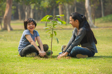 Smiling brother and sister planting a small plant in garden and sitting beside it.