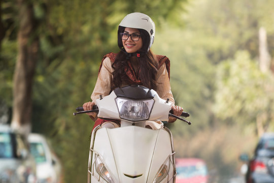 Smiling young woman wearing eyeglasses and helmet riding scooter looking away.