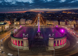Budapest, Hungary - Aerial drone view of the famous Heroes' Square (Hosok tere) lit up in unique purple and pink color by night with a colorful sunset