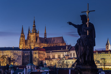 Prague, Czech Republic - Illuminated St.Vitus Cathedral at dusk with clear blue sky taken from Charles Bridge on a winter night. Out of focus statue in foreground