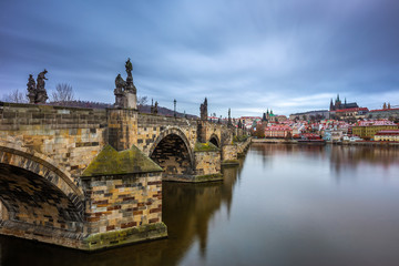 Prague, Czech Republic - The world famous Charles Bridge (Karluv most) with River Vltava and St. Vitus Cathedral on a cludy winter morning