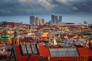 Prague, Czech Republic - Aerial skyline view of Prague at winter sunset with red rooftops, cloudy sky and skyscrapers at business district