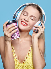 Young pretty happy woman in yellow dress drinking coffee and listening to music in headphones