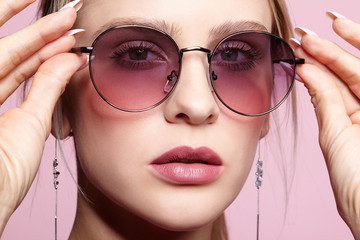 Close-up portrait of attractive young woman in tinted glasses on pink background