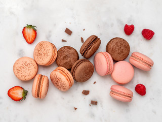 Zelfklevend Fotobehang Macarons Composition with french macarons on white marble background. Top view of colorful pastel macaroons or macaron with berries and chocolate