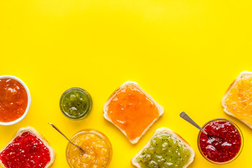 Toast with colorful fruit jam frame on yellow background frame copy space