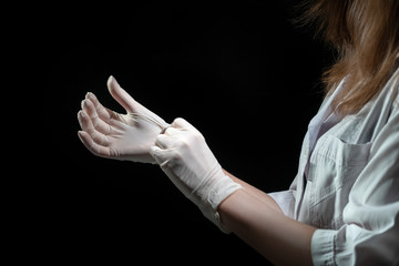 Lady doctor puts on rubber medical white gloves on dark background