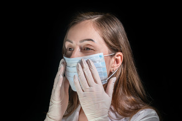 Young female doctor puts on white protection mask on dark background
