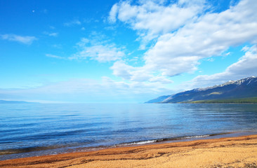 Lake Baikal on a sunny June day. The beautiful sandy beach of the Barguzin Bay and the mountain snowy peaks of the Holy Nose Peninsula. Natural summer background