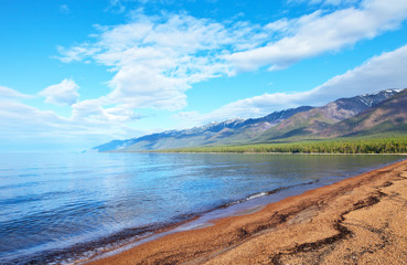 Baikal Lake on a sunny June day. The long sandy beach of Barguzin Bay is famous for tourists with calm warm water and beautiful mountain landscapes. Natural summer background